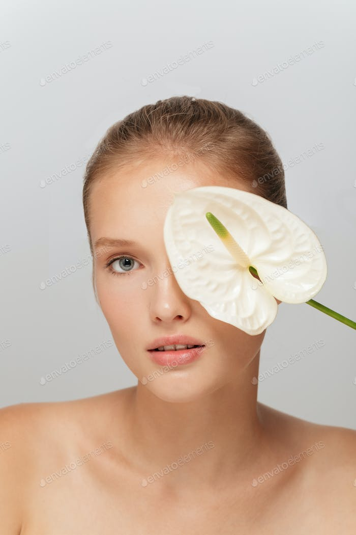 Portrait of young beautiful woman without makeup covering eye wi