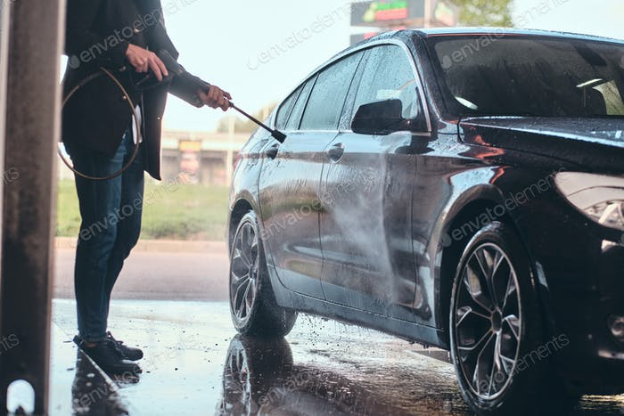 Busy man is washing his own car at car washing station.