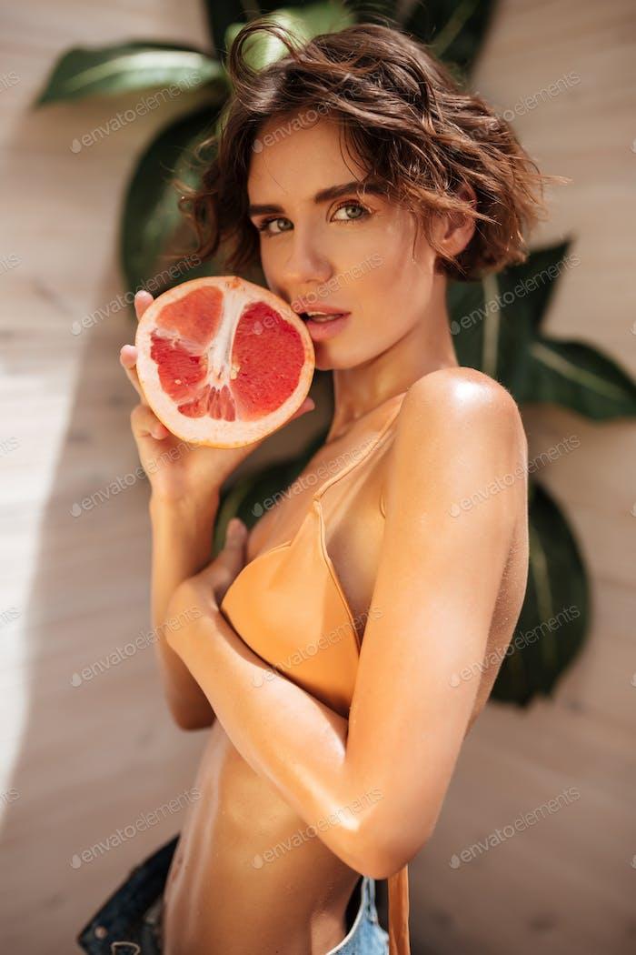 Junge nette Mädchen stehend mit Grapefruit auf Holzhintergrund