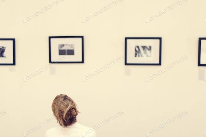 People looking at frames in an exhibition