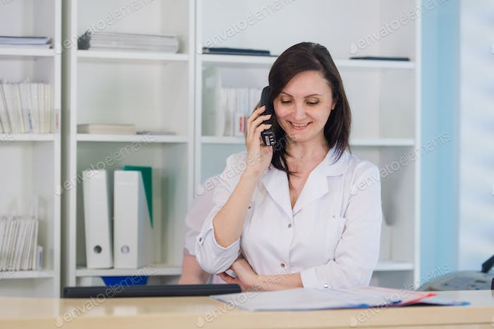 Young practitioner doctor working at the clinic reception desk, she is answering phone calls and