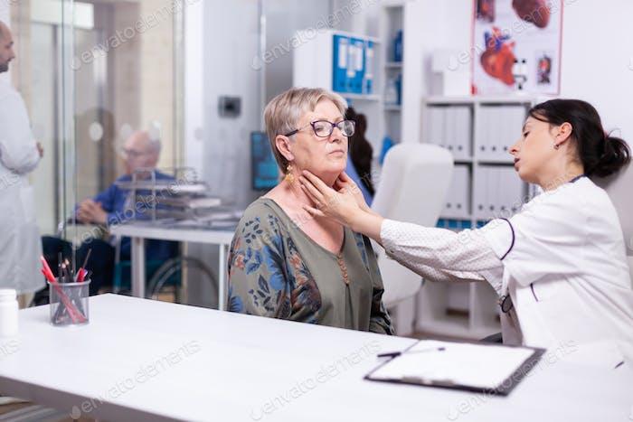 Facharzt überprüft Nackenlymphknoten der alten Frau