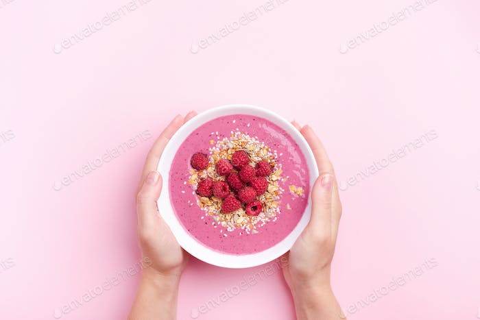 Female`s Hands Holding Raspberries Smothie Bowl on Pink Background.