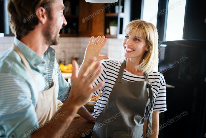 Junge glückliche Frau und Mann sind hoch fünf einander in Küche