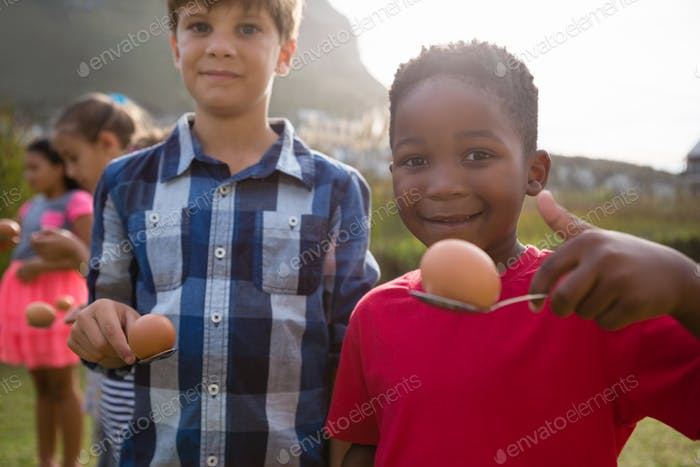 Portrait of boys playing egg and spoon race