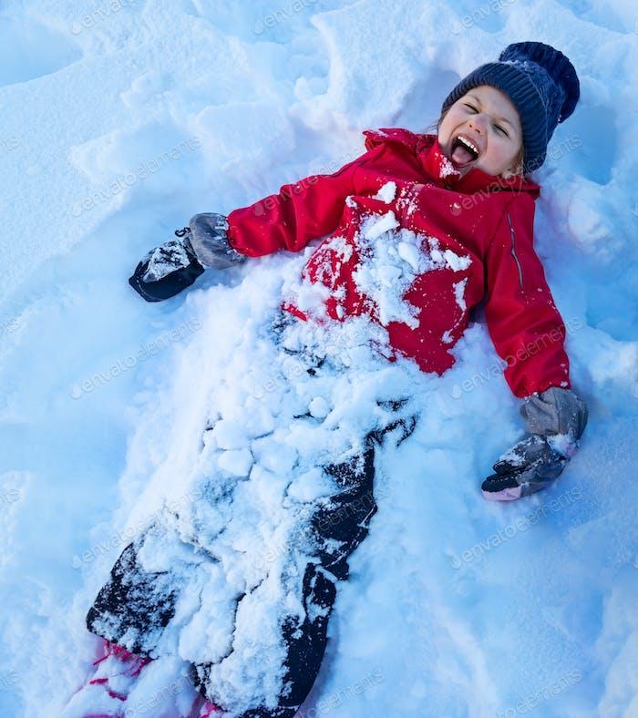 Niña jugando ángel de nieve