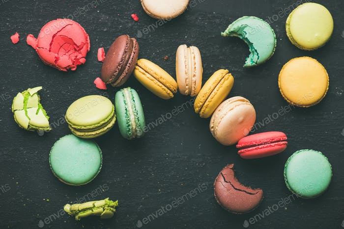 Flat-lay of colorful French macaroons over black background