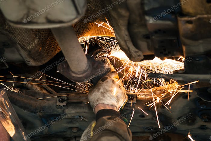 serviceman cleans muffler pipe by angle grinder