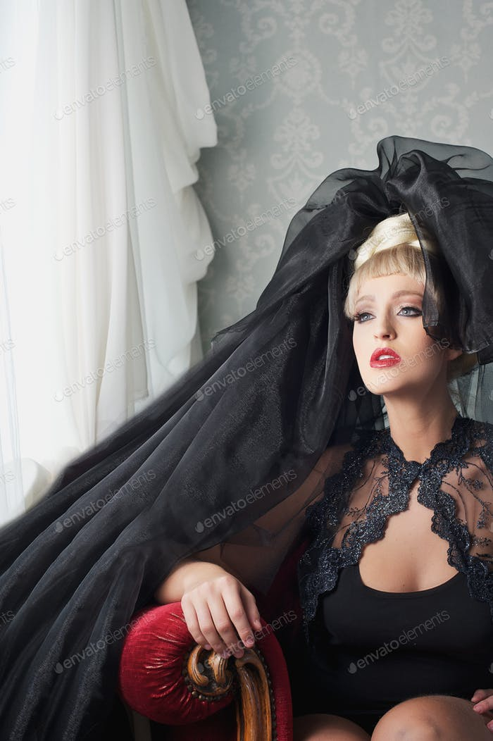 Blond Fashion Woman Sitting with Black Head Dress
