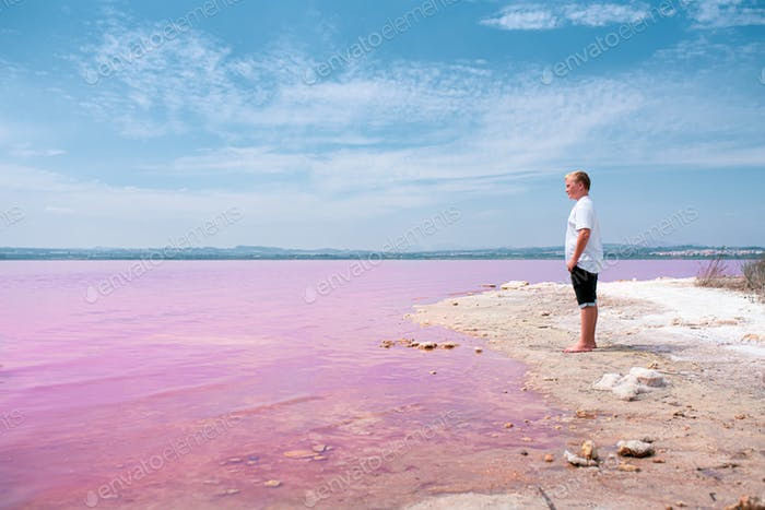 cute teenager boy wearing summer clothes standing on pink lake