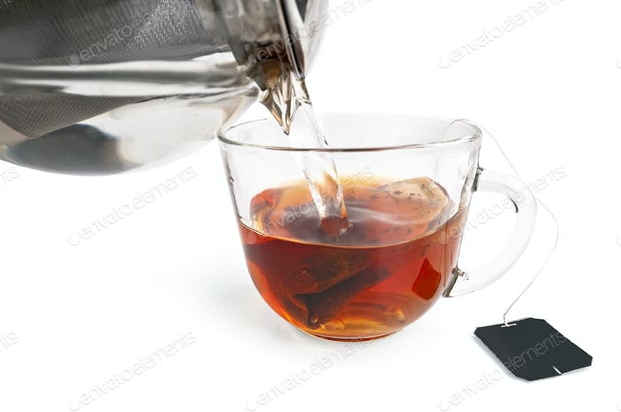 Tea from a bag in a glass cup with a teapot