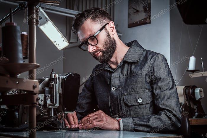 Modedesigner näht Kleidung durch Nähmaschine in der Werkstatt.