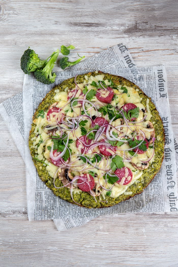 Crust Broccoli base low carbs keto pizza with salami, avocado on vintage newspapper