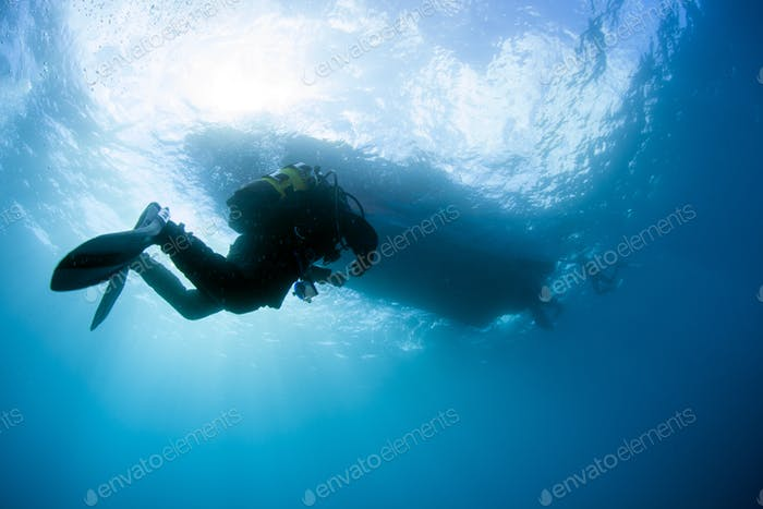 A Diver Ascends to a Waiting Boat Silhouette