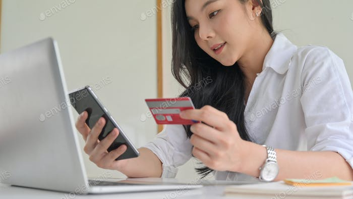 Young women are using smartphone and credit card with laptop.
