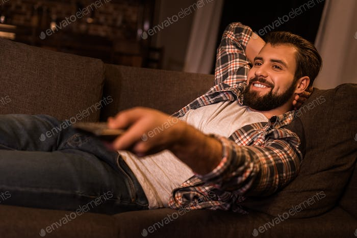 young man laying on couch and watching tv at home