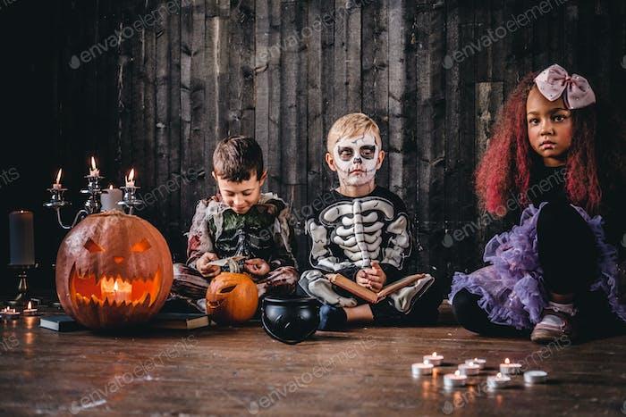 Halloween-Party mit Gruppenkindern, die zusammen auf einem Holzboden in einem alten Haus sitzen