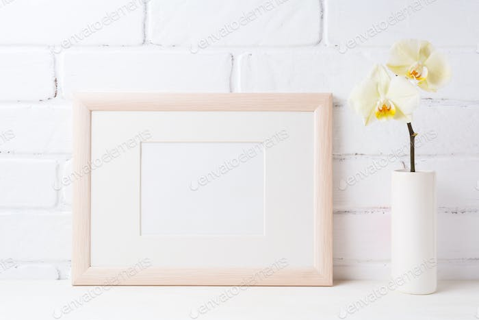 Wooden landscape frame mockup with soft yellow orchid in vase