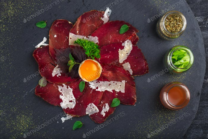 Charcuterie board with italian bresaola cured beef, parmesan cheese, close view