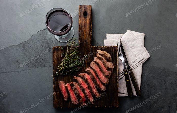 Scheiben Rindfleisch mittelseltenes Steak auf Holzbrett, Glas Rotwein auf Schiefergrund