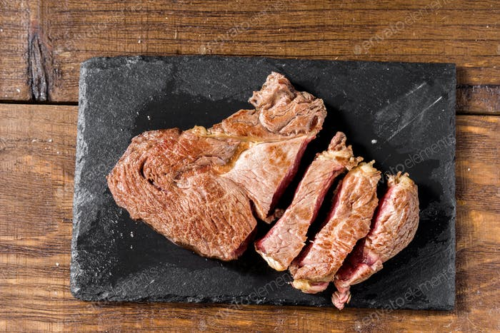 fillets of grilled horse meat on black stone
