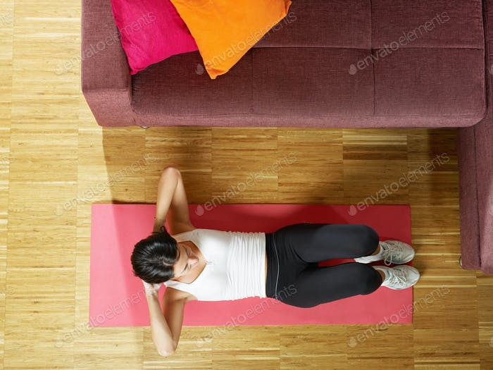 Woman Doing Abs Abdominals Exercise On Pad At Home