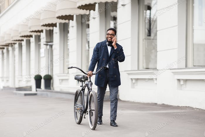 Afro businessman walking with bike and talking on phone