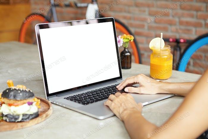 Abgeschnittenes hinteres Porträt einer selbständigen Frau, die einen Laptop für ferne Arbeit benutzt, während sie Mea hat