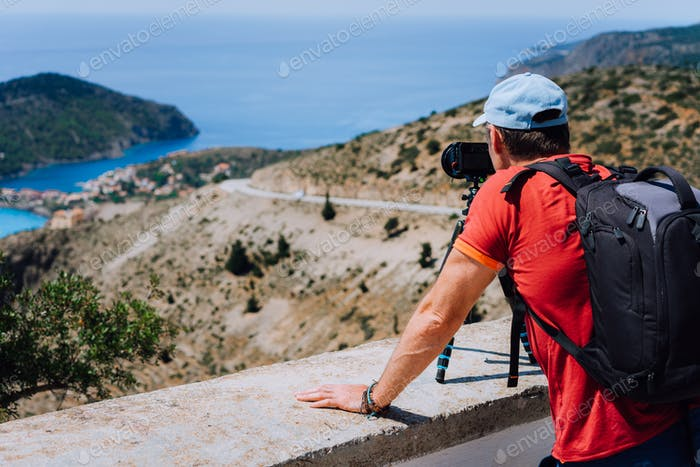 Visiting Kefalonia Greece Europe. Summer holiday weekend. Male freelance photographer with backpack