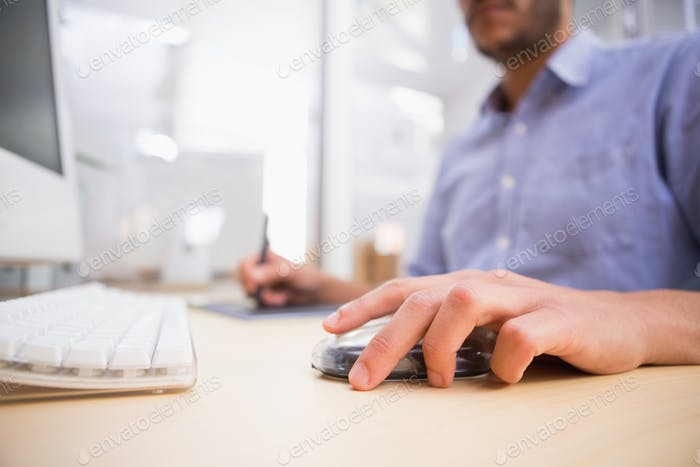 Side view mid section of man working at desk with computer and digitizer