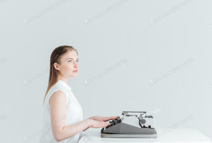 Pensive woman typing on retro machine