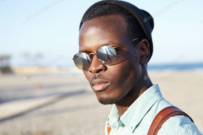 Cierra el verano retrato al aire libre del apuesto estudiante afroamericano de moda en lente de espejo cantado