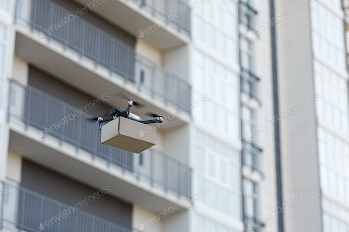 Modern quadrocopter robots delivering packages , blurred city, copy space
