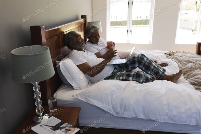 Couple drinking cup of coffee in bedroom at home