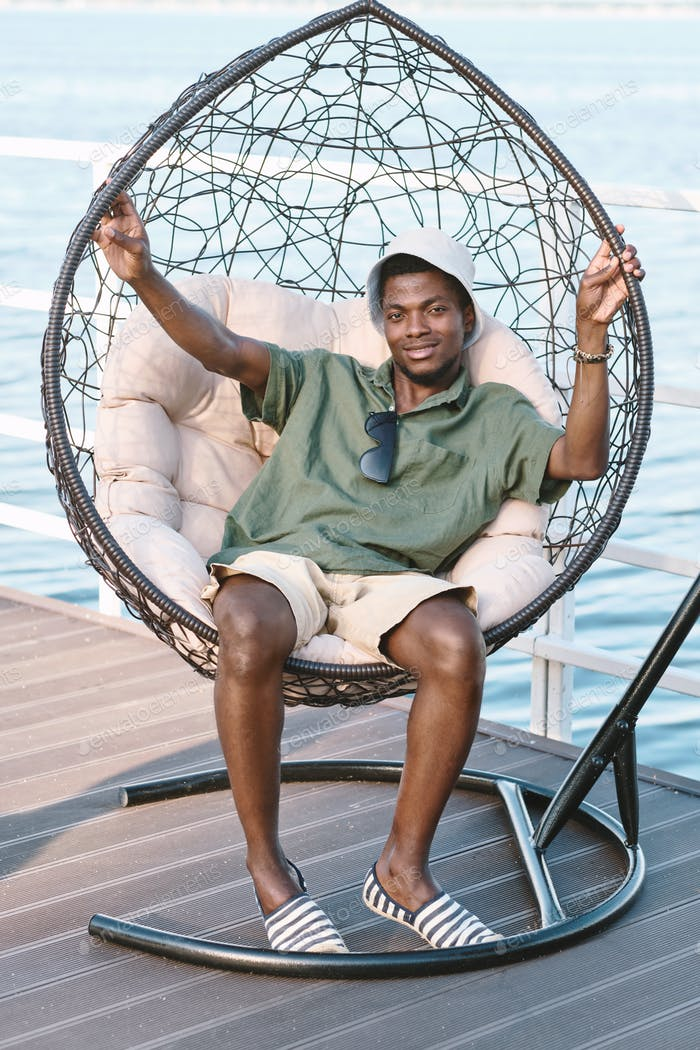 Happy young African man in casualwear sitting in comfortable armchair