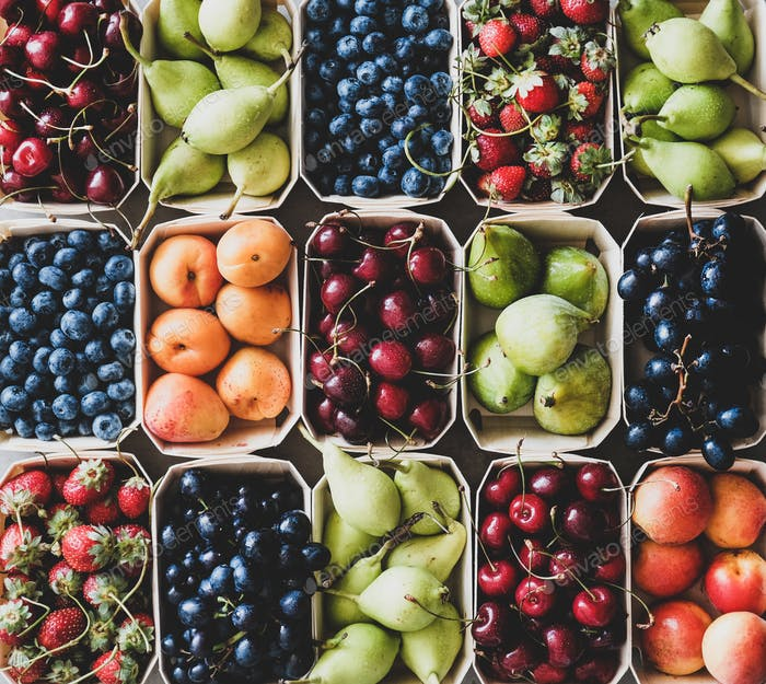Fresh summer fruits and berries in eco-friendly wooden boxes , close-up