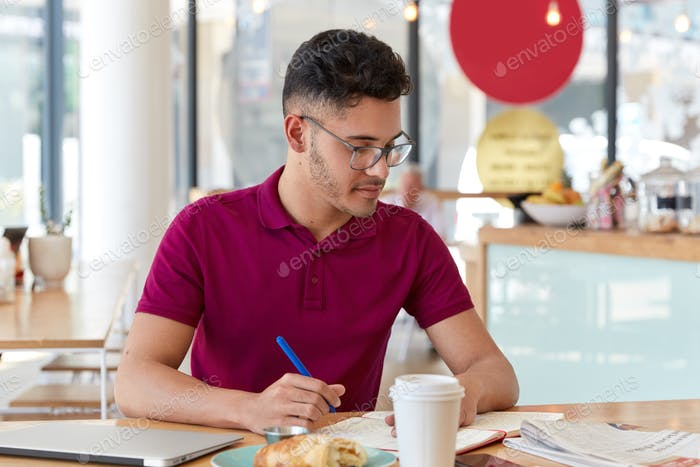 Photo of mixed race male student writes necessary information in notepad from daily newspaper, creat