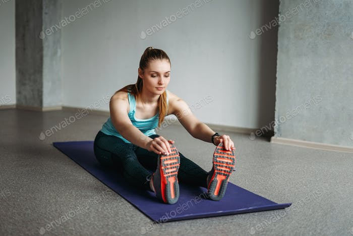 Young woman in sport wear fitness girl doing stretching at home studio