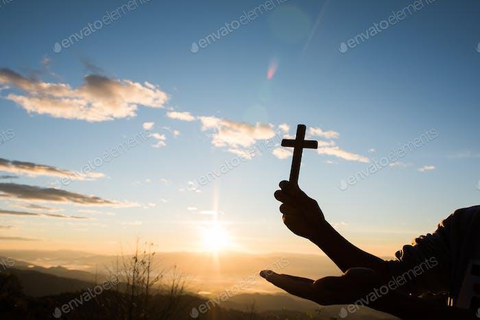 Silhouette der Hand halten Kreuz von Gott