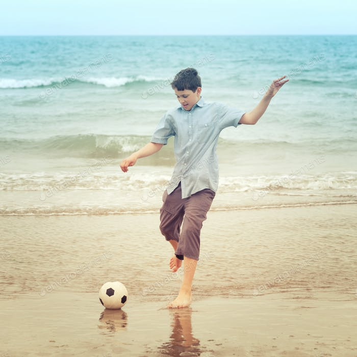 Boy on the beach kiking the football
