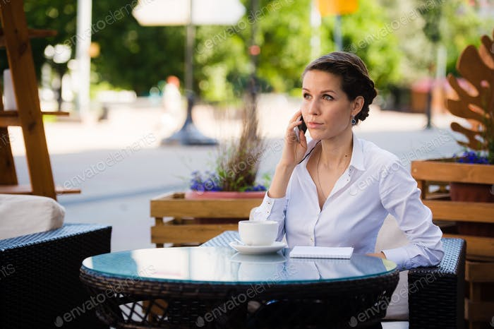 Good business talk. Cheerful young businesswoman talking on the mobile phone and holding cup of