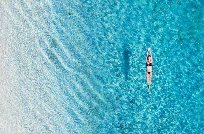Das Mädchen schwimmt im blauen klaren Wasser. Der Blick aus der Luft. Bali, Indonesien