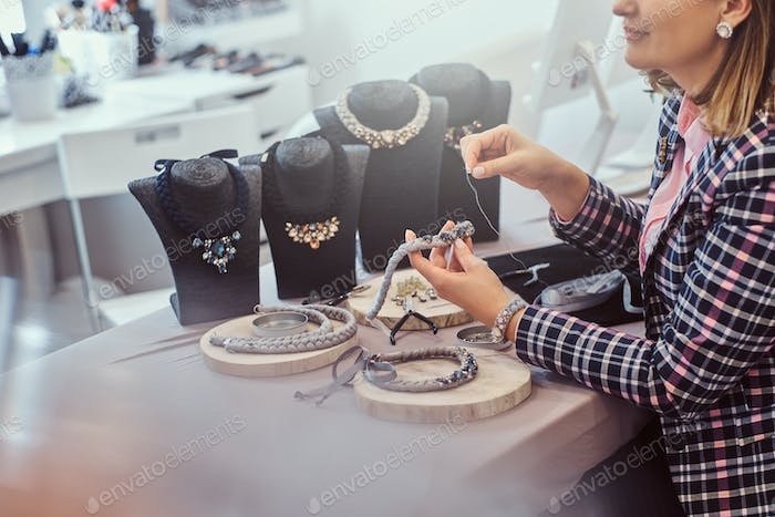 Elegantly dressed woman makes handmade necklaces, working with needles and thread in workshop.