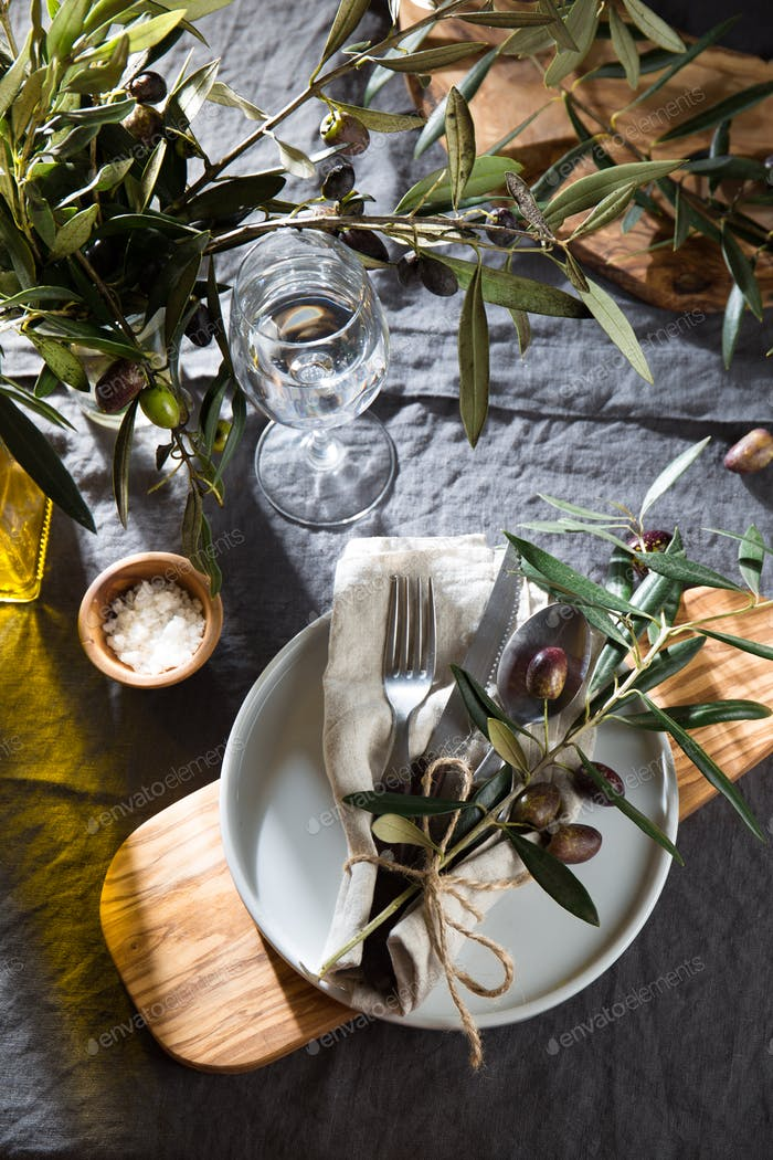 Table setting with gray Linen tablecloth, plate, cutlery, olive tree branch decoration