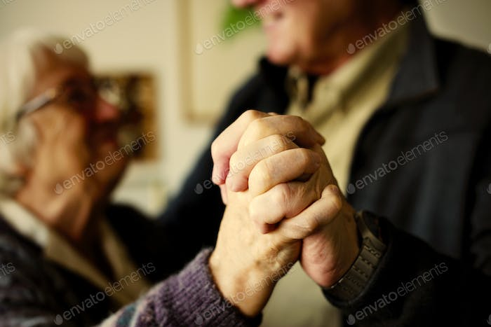 Close up of senior couple's hands as they are dancing