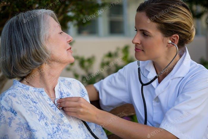 Doctor listening to heart beats of senior woman