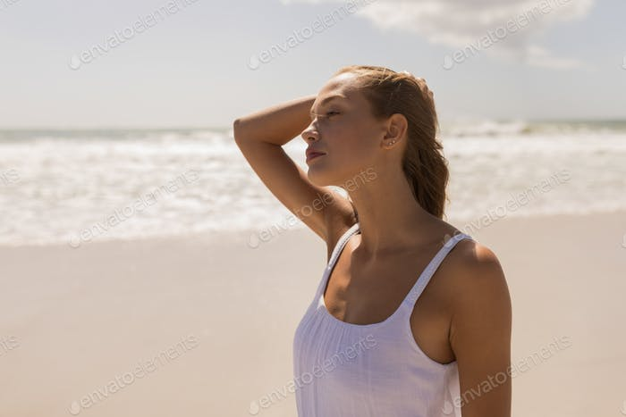 Side view of beautiful young woman with hand on head standing at beach in the sunshine