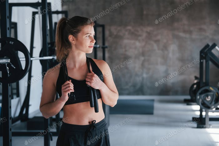 Black colored jumping rope. Photo of gorgeous blonde woman in the gym at her weekend time
