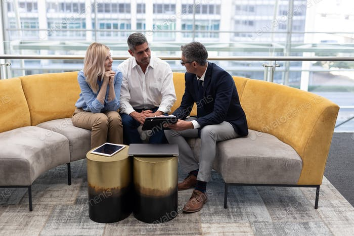 Business executives interacting with each other sitting on the sofa in office