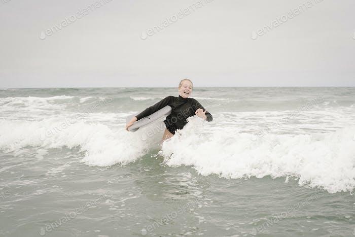 Blondes Mädchen Bodyboarding im Ozean.
